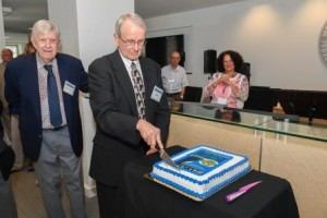Acting Director John Pinto slices an FMCS anniversary cake, and former Director Ken Moffett observes.